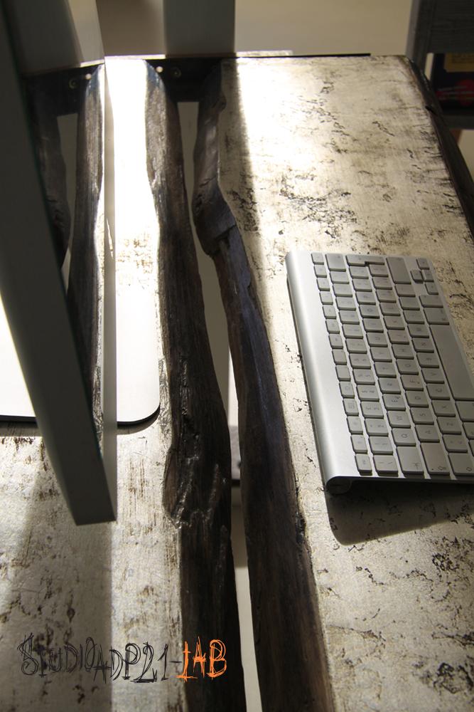 dettaglio di tavolo sospeso realizzato con tavole naturali, rivestite con foglia in argento