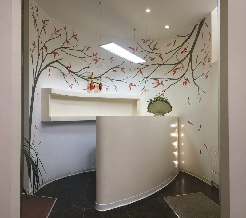 alberi dipinti su parete dietro reception studio medico-alberi dipinti in marrone, fogli in arancio ossido