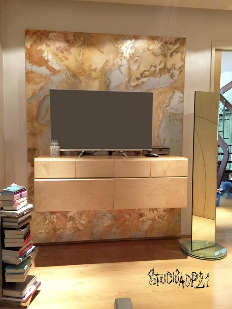 parete tv decorata con cassettiera a sospensione.decoro in foglia argento e pigmenti naturali ocra