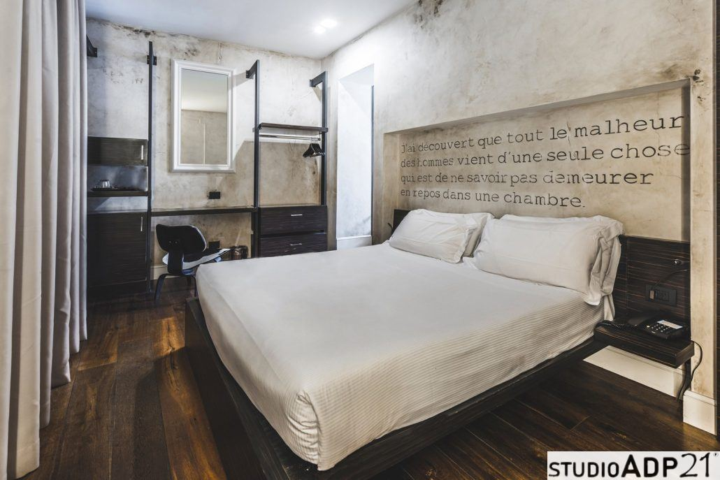 stanza hotel decorata con patine leggere sui toni sabbia e terre naturali.scritte su pareti